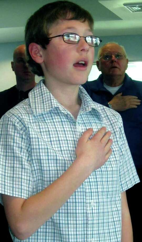 SPECTRUM/Dillon Ash, the 10-year-old of New Milford policeman Larry Ash, leads those on hand in the Pledge of Allegiance before the March 18, 2011 ceremony for the promotion of his father, Larry Ash, to lieutenant at the New Milford Police Department. The swearing in at the Community Ambulance facility also witnessed the promotion of  Sgt. James Dzamko and Sgt. Edward Hannan. Photo: Norm Cummings / The News-Times
