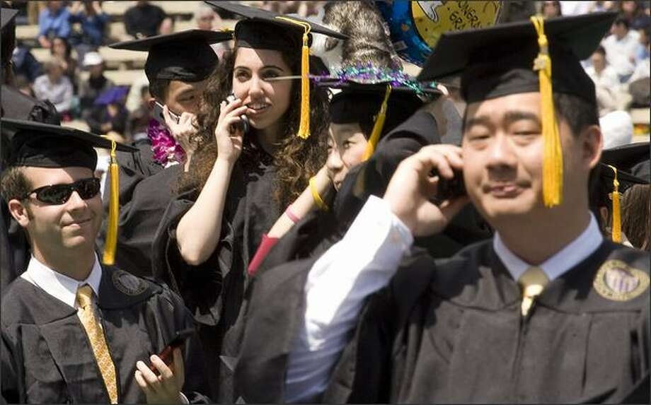 Graduates try to reach friends and parents in the stands via cell phone. Photo: Grant M. Haller/Seattle Post-Intelligencer