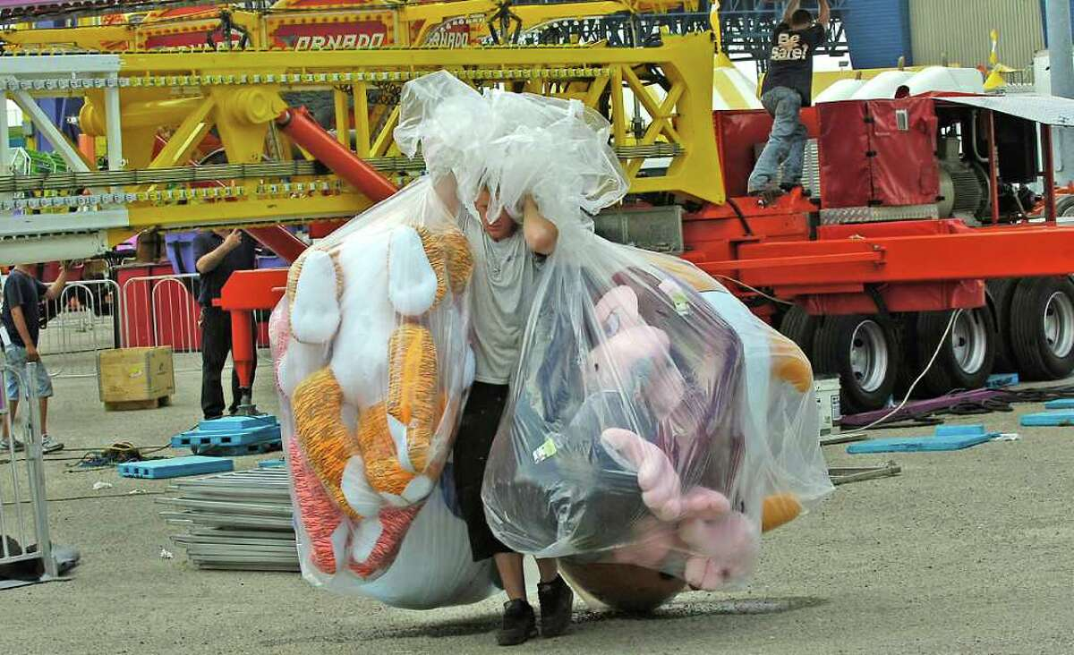 Mike Stanley, with Stephanie Concessions, brings another load of the very large official prizes to a gaming booth as Wednesday brought a flourish of last minute details that had to be completed along the Midway. The South Texas State Fair which officially kicks off Thursday and runs through Sunday, April 3, 2011. Dave Ryan/The Enterprise