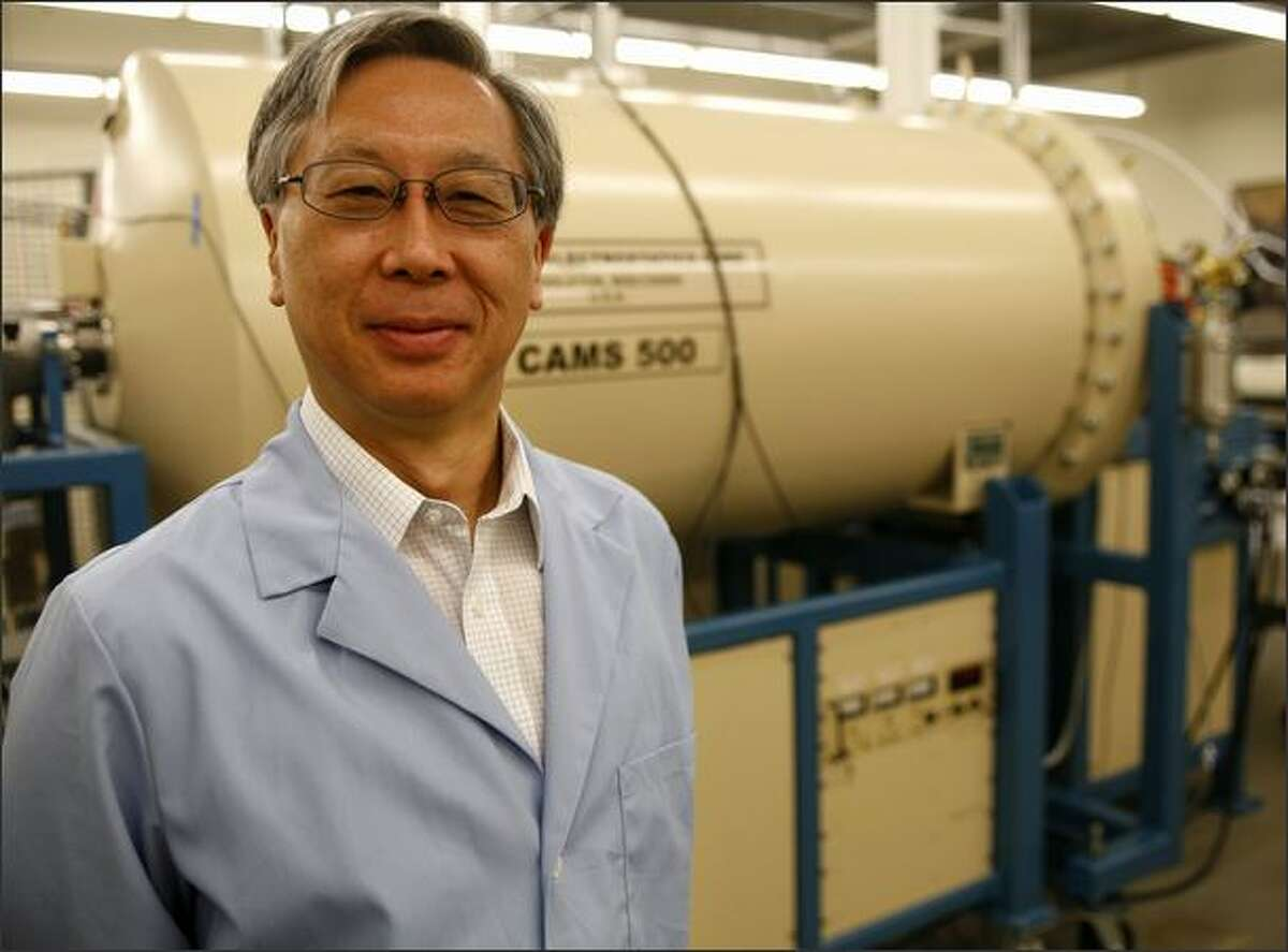 Glenn Kawasaki, CEO of Accium BioSciences, stands next to the accelerated mass spectrometer, which generates a charge of a half-million volts in its drumlike container and speeds carbon particles through its system at one-tenth the speed of light.