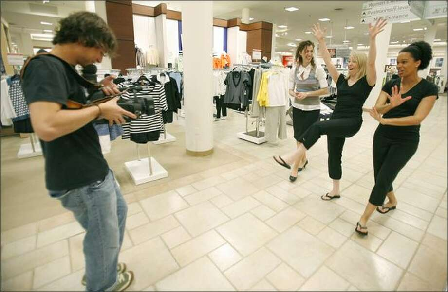Brett Renville films Whitney Keyes, center, and Wyatt Bardouille, right, shopping at Macy's in Northgate with freelance stylist Mayna Sgaramella for a segment of their Web show. Keyes, Bardouille and their crew spent four hours setting up before filming the two women's makeovers. Photo: Paul Joseph Brown/Seattle Post-Intelligencer