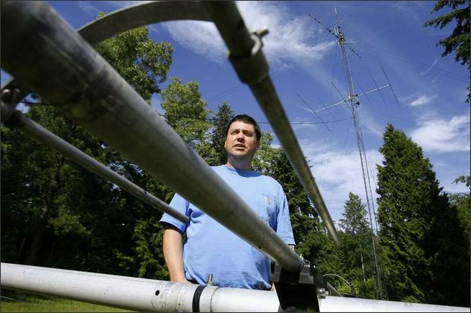 Mike Dinkelman, aka November 7 Whiskey Alpha, stands near an antenna at his Kent home. He and other ham operators will gather this weekend for Field Day, an amateur radio holiday that gives them a chance to practice their skills. Photo: Gilbert W. Arias/Seattle Post-Intelligencer
