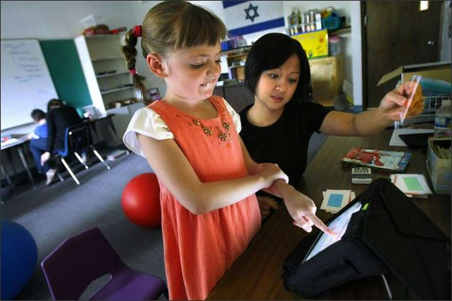 Morgan Brewer, 8, works with Lovelle Suarez to answer a matching problem at the Academy for Precision Learning, which uses individual programs for its students. Photo: Andy Rogers/Seattle Post-Intelligencer