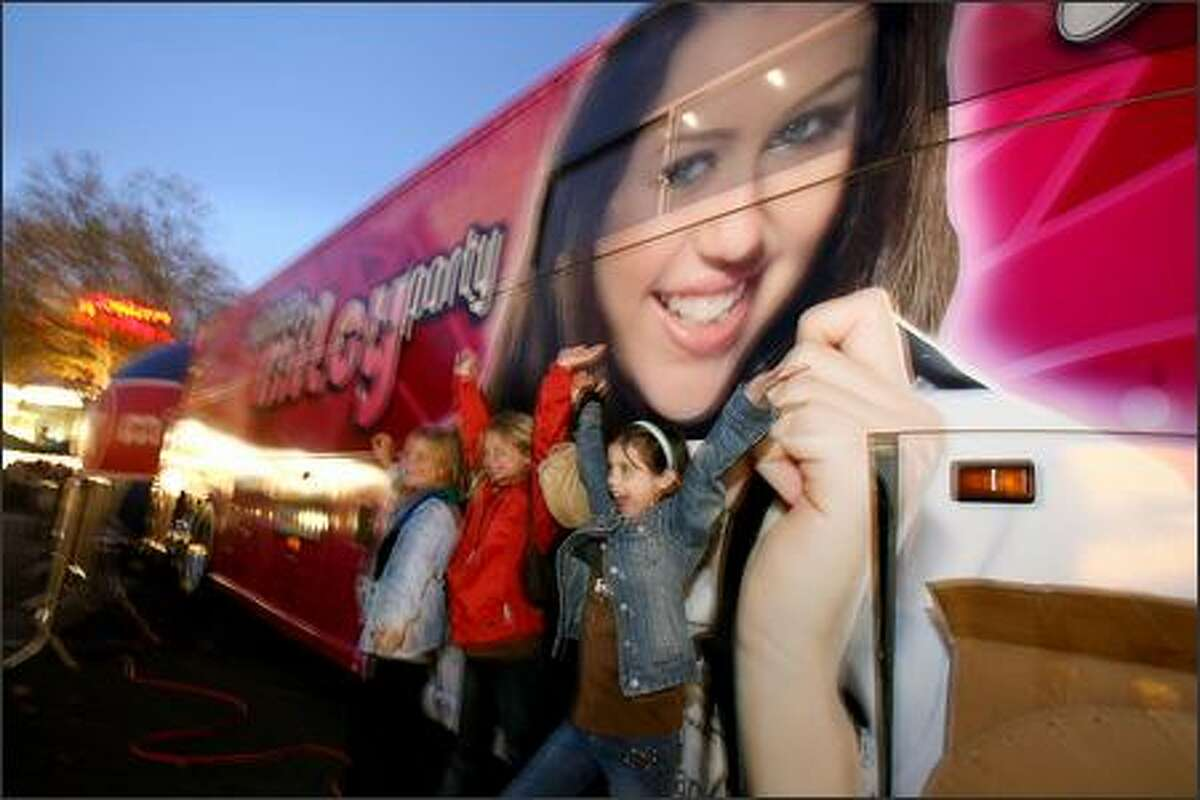 Kelsy Byus, of Spokane flashes a smile next to the the Miley Cyrus aka Hannah Montana bus just before the concert at Key Arena in Seattle.