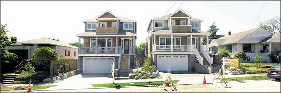 Two houses in the 6700 block of Seventh Avenue Northwest dwarf the homes on either side. Megahomes may mean more money for developers, but owners of smaller neighboring houses aren't pleased. Photo: Grant M. Haller/Seattle Post-Intelligencer