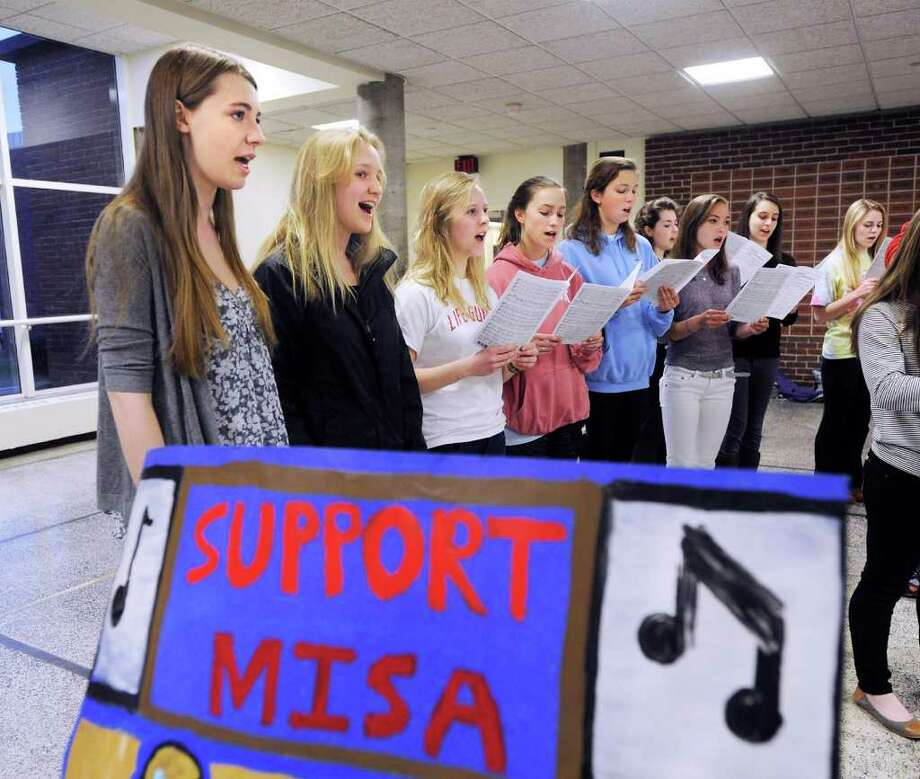"At left, Lindsay Anibal, 17, a Greenwich High School junior, and fellow students perform in a hallway near the Greenwich High School auditorium prior to a Board of Education community forum on the Greenwich High School Music Instructional Space and Auditorium Project (MISA) Wednesday night, March 23, 2011.  The students' sign says,""Support MISA."" Photo: Bob Luckey / Greenwich Time"