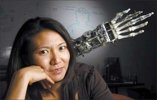 A robotic arm, complete with rough surfaces on the finger bones, reaches out from behind Yoky Matsuoka, UW associate professor of computer science and engineering. Photo: Andy Rogers/Seattle Post-Intelligencer