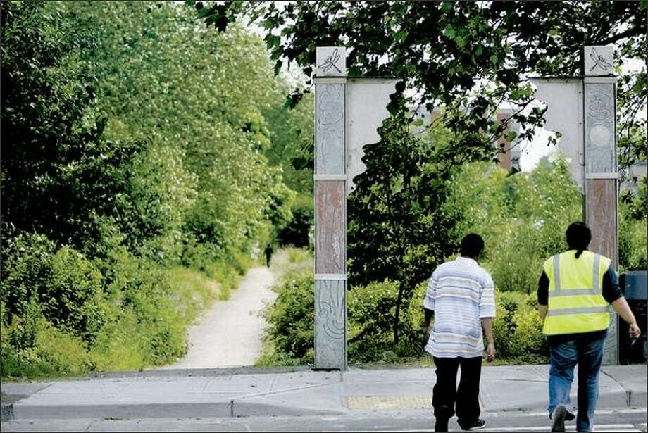 Decorative marker posts, courtesy of the Pomegranate Center, draw the attention of two people at Longfellow Creek trail at Roxhill Park. Photo: Grant M. Haller/Seattle Post-Intelligencer