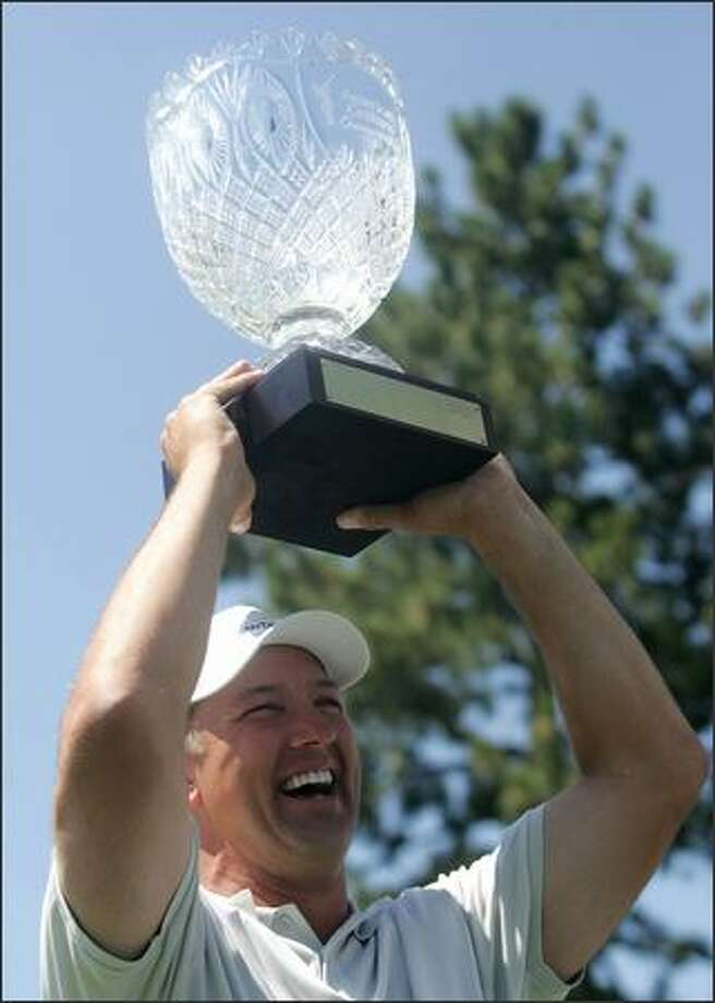 Chris Chandler hoists the trophy after winning the American Century Championship in 2007. Photo: / Associated Press