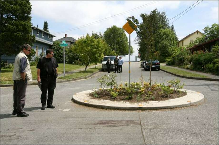 Seattle Police detectives survey the Rainier Beach traffic circle where James Paroline, 60, was badly beaten during an altercation Wednesday night. Paroline died from his injuries Thursday night at Harborview Medical Center. Photo: Dan DeLong/Seattle Post-Intelligencer