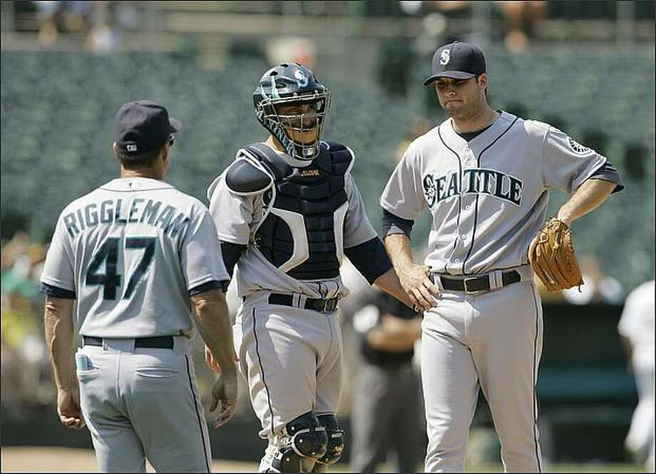 Mariners manager Jim Riggleman, left, walks out to the mound to remove pitcher Brandon Morrow, right, during the ninth inning of Thursday's game in Oakland. Mariners catcher Jamie Burke looks on. Photo: / Associated Press