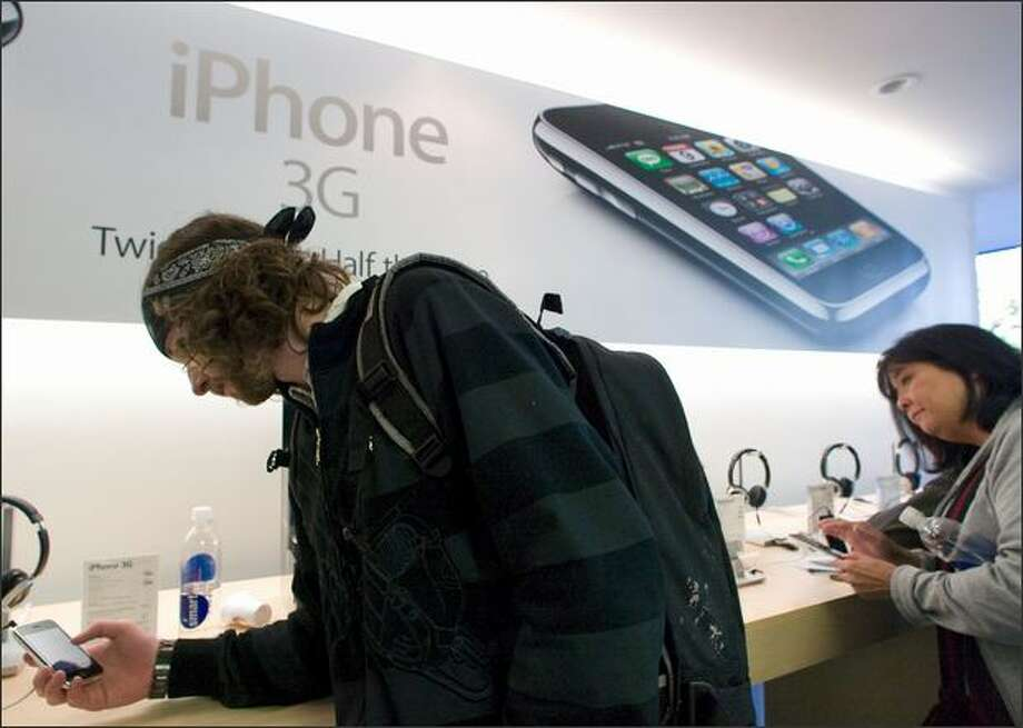 Isaac Prince, who had been in line since 3 a.m., uses an iPhone 3G at the University Village Apple Store on Friday. AT&T officials said the server problems were global. Photo: Jim Bryant/Seattle Post-Intelligencer