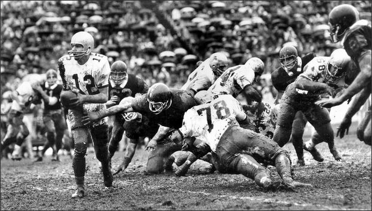 1968: Hank Grenda, left, looks to hand off during the WSU-Washington game in Spokane. Grenda led the Cougars to a 24-0 victory.