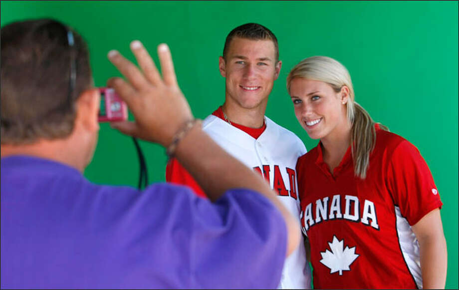Russ Lawrie of Langley, B.C., snaps a photo of son Brett, a touted major league draft pick, and daughter Danielle, a record-setting UW softball pitcher. Photo: Andy Rogers/Seattle Post-Intelligencer