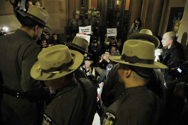 New York State Troopers gather to begin the process of arresting CUNY faculty from the Professional Staff Congress and supporters from community groups, and colleges as they protest inside the Capitol over Governor Andrew Cuomo's proposed cuts to CUNY community colleges, on Wednesday, March 23, 2011.  Several protestors were arrested when they blocked a doorway on outside the Governor's wing of the Capitol and refused to move.  (Paul Buckowski / Times Union) Photo: Paul Buckowski  / 00012506A
