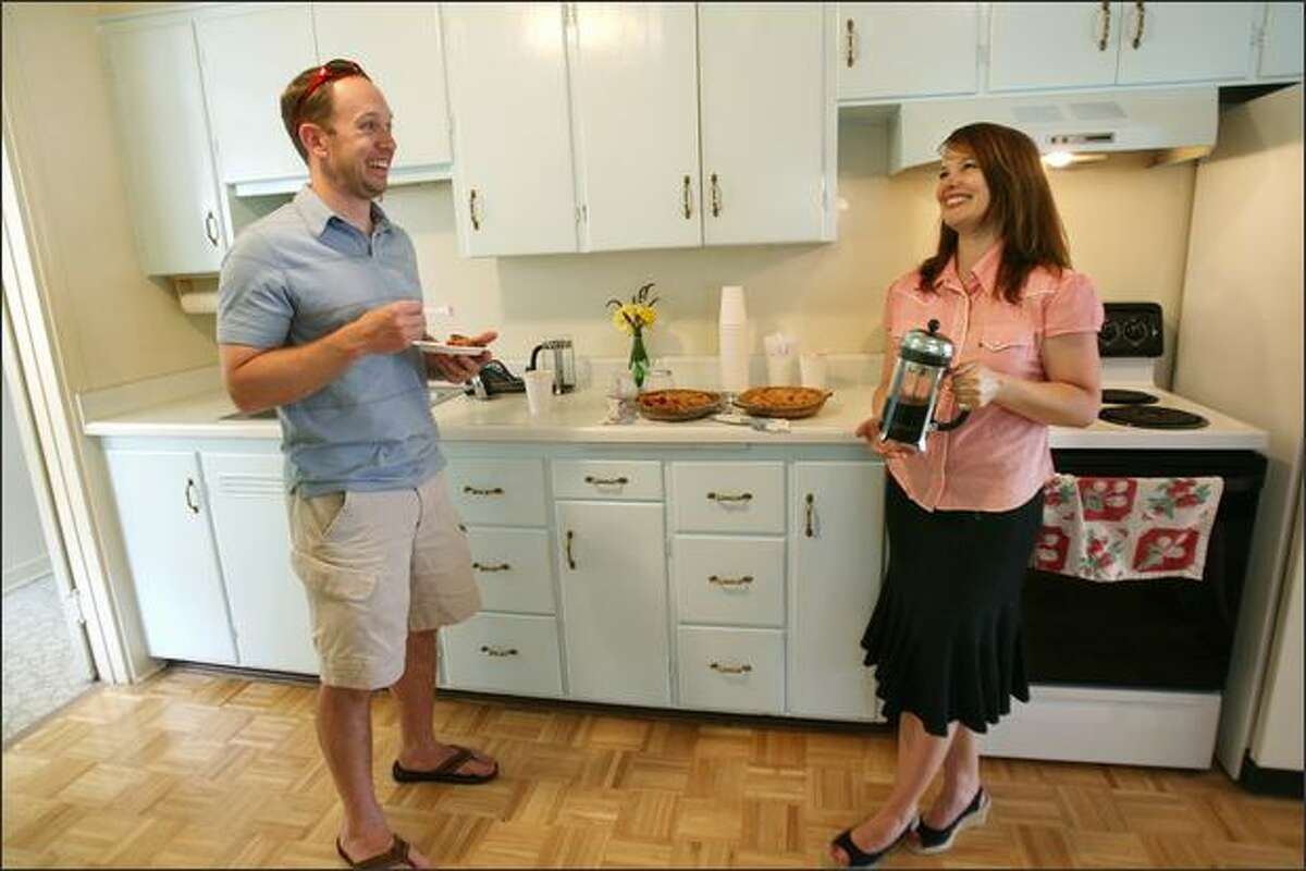 Jeff Houser, a condo owner interested in buying a house, talks with RE/MAX Mutual Realty agent Mary Schile while enjoying a piece of pie during an open house in Seattle's Greenwood neighborhood. Schile regularly bakes pies at the homes she's showing to potential buyers.