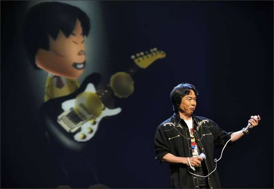 "Legendary game designer and senior managing Director, Shigeru Miyamoto demonstrates the new game ""Wii Music"", by playing virtual guitar during the Nintendo E3 media briefing at the Kodak Theater in Hollywood, Calif., Tuesday. (GABRIEL BOUYS/AFP/Getty Images) Photo: /"