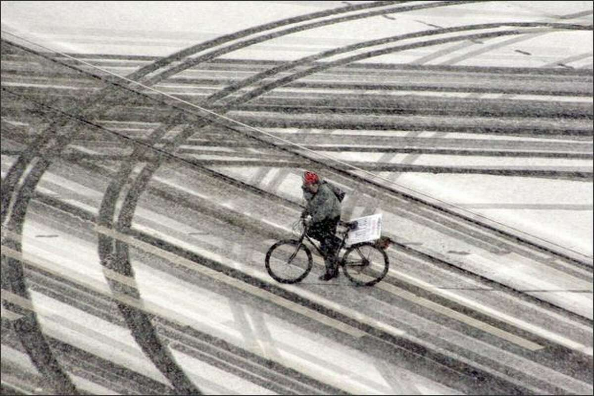 A bicyclist crosses the intersection of Westlake Avenue and Eighth Avenue in downtown Seattle as snow hit the city Saturday afternoon.