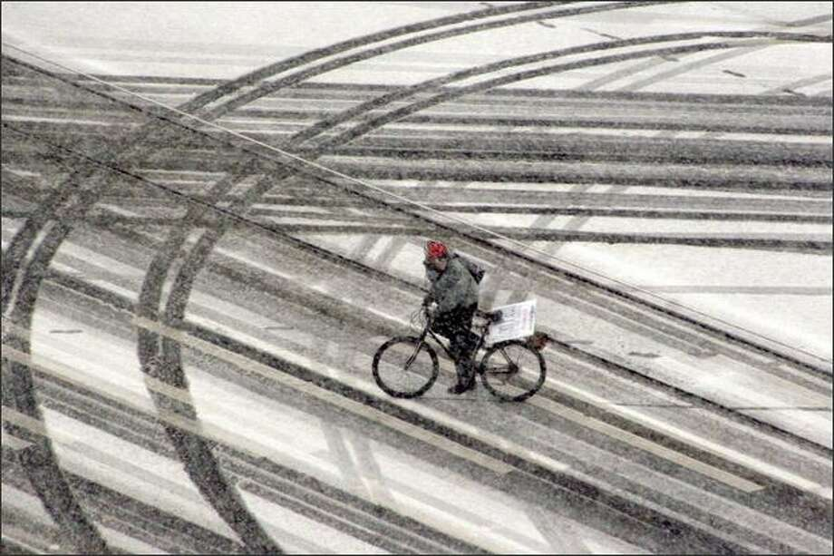 A bicyclist crosses the intersection of Westlake Avenue and Eighth Avenue in downtown Seattle as snow hit the city Saturday afternoon. Photo: Robert Sumner, P-I