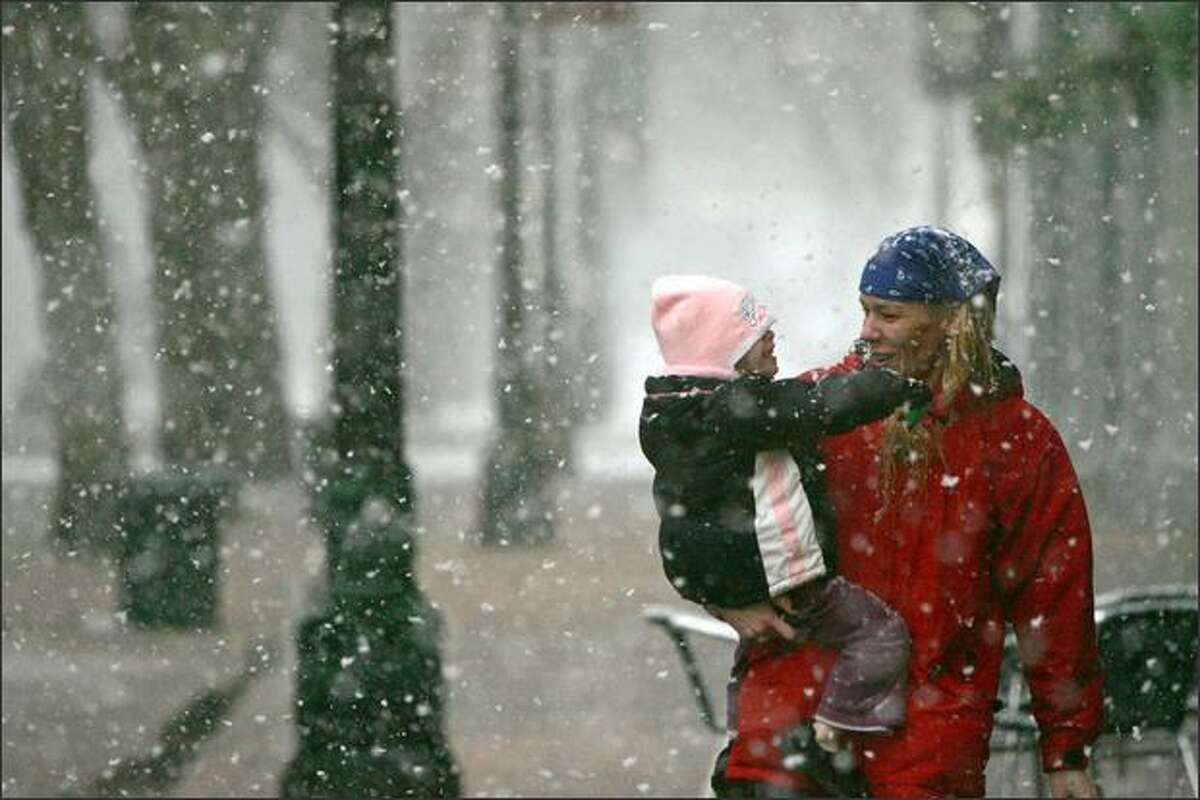 Kimberly Swartz and daughter Alex Anicello make their way through downtown during Saturday's snowfall.