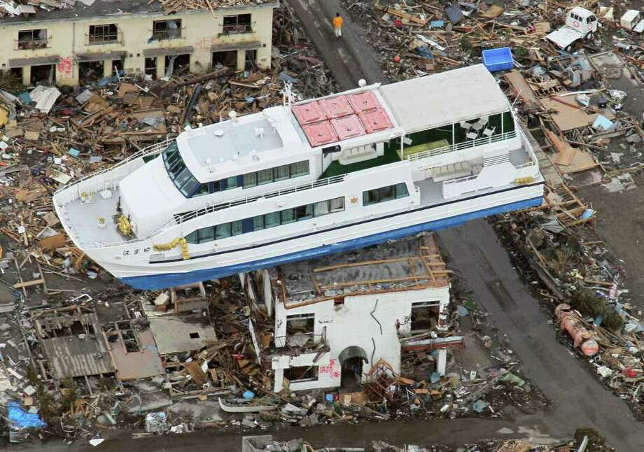 A sightseeing boat washed away by the March 11 tsunami sits on a ruined building in Otsuchi, Iwate Prefecture, Japan, Wednesday March 23, 2011. (AP Photo/Kyodo News) JAPAN OUT, MANDATORY CREDIT, NO LICENSING IN CHINA, HONG KONG, JAPAN, SOUTH KOREA AND FRANCE Photo: SUB / Beaumont