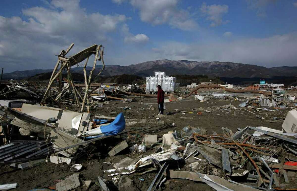 A survivor walks through debris looking for value things in the March 11 earthquake and tsunami-stricken town of Rikuzentakata, Iwate Prefecture, northern Japan Wednesday, March 23, 2011. (AP Photo/Vincent Yu)