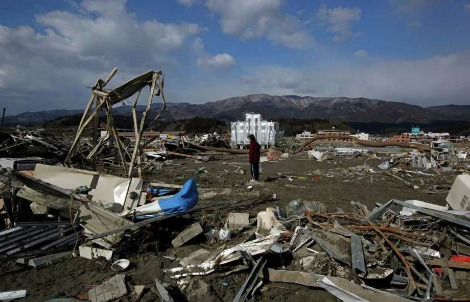 A survivor walks through debris looking for value things in the March 11 earthquake and tsunami-stricken town of Rikuzentakata, Iwate Prefecture, northern Japan Wednesday, March 23, 2011. (AP Photo/Vincent Yu) Photo: Vincent Yu, STF / Beaumont