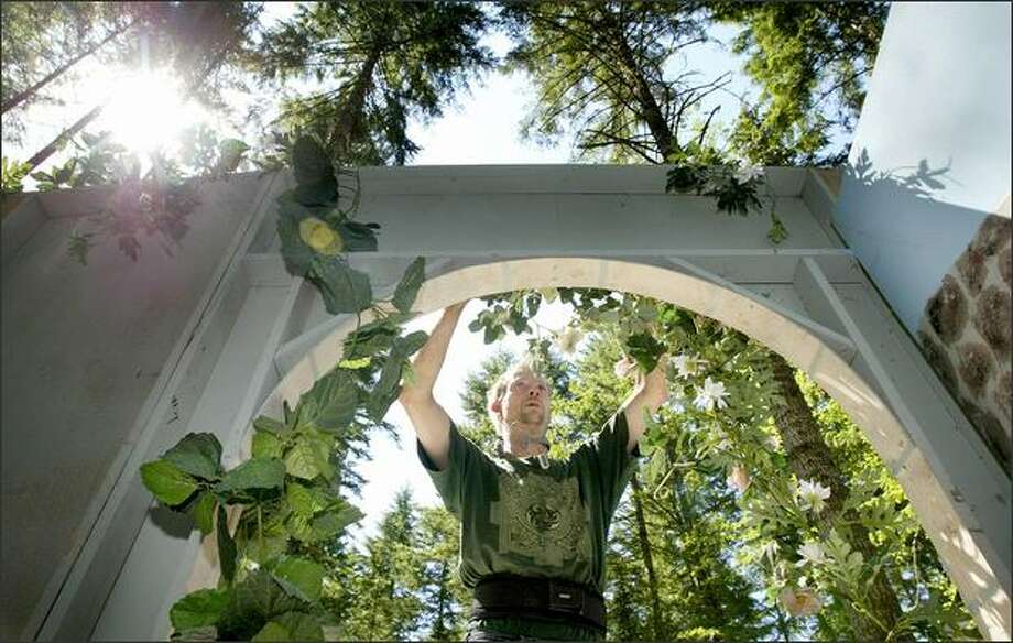 Dann Porter, groundskeeper for the Washington Renaissance Fantasy Faire, decorates the Queen's Stage in Belfair with woodland floral arrangements. Organizer Ron Cleveland learned Monday that the fair was canceled because of permit problems. (Kitsap Sun, Larry Steagall) Photo: / Associated Press