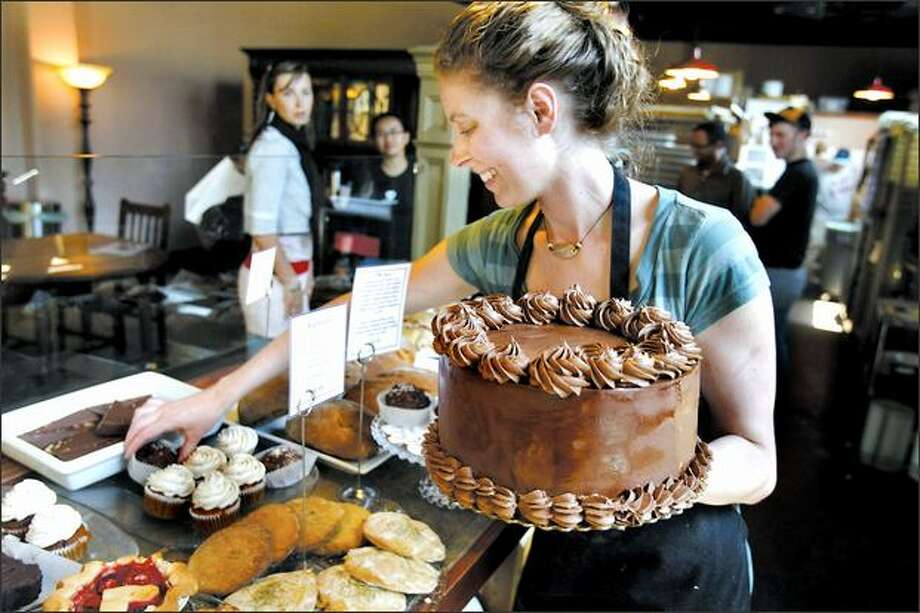 Brittany Higley places a vegan chocolate cake in the case at Flying Apron bakery in Fremont. Flying Apron's baked goods are made without gluten, egg and dairy products. Photo: Meryl Schenker/Seattle Post-Intelligencer