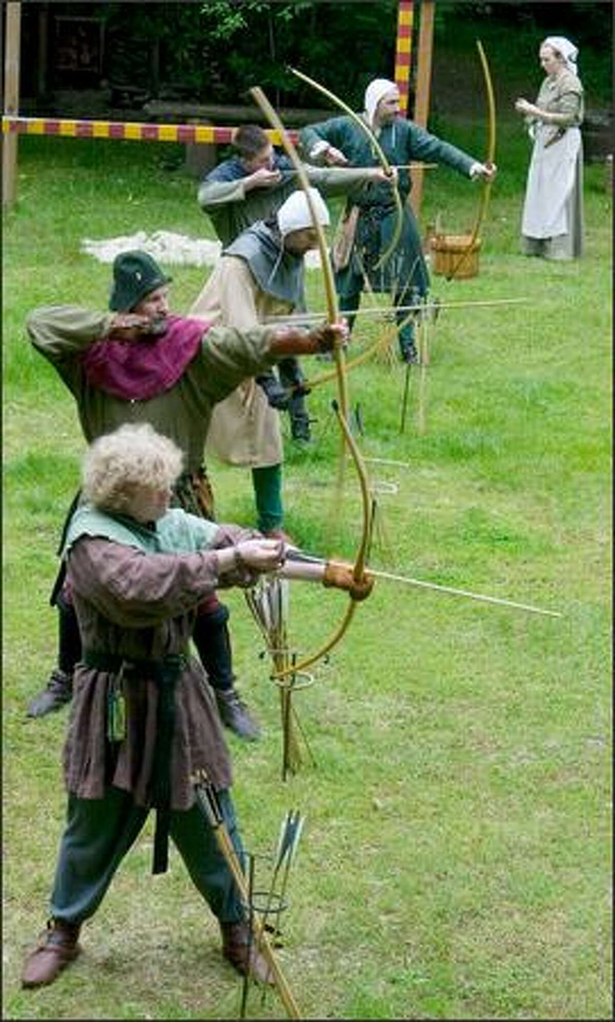 From bottom to top: James, Richard, Nicholas, Christopher and David take aim at targets on the archery range at Camlann. The village, set on 36 acres, is a living history project portraying rural England in 1376.