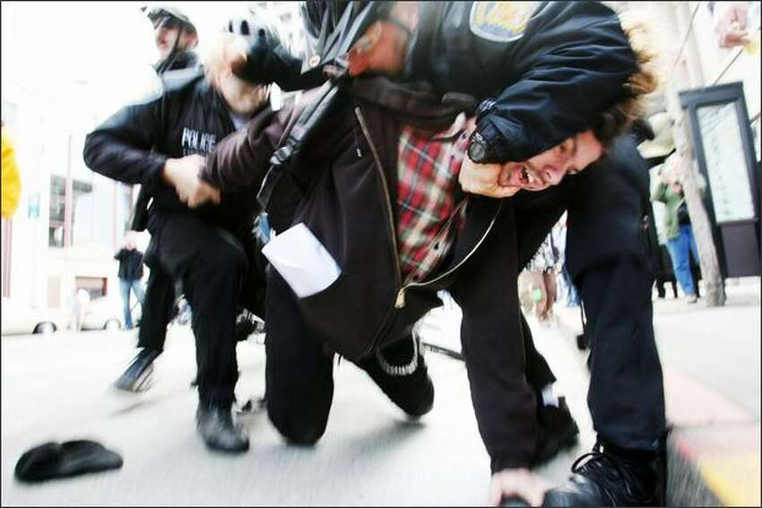 Seattle Police officers wrestle an anti-war protester to the ground during a protest to mark the four-year anniversary of the Iraq war.Eklund: Sometimes stupid luck can turn out all right. It happened in this photo when I had come from another assignment and was shooting at an ISO that was too low and an aperture that was too high, which resulted in a slow shutter speed. The camera was set at 250 ISO and the exposure was 1/25 of a second at f/7.0. Way too slow to be shooting news, but this happened within minutes of arriving at the protest march. Fortunately the focus was right on and I was moving with the subject, and I think the police had his head in a hammerlock, so there actually wasn't any movement there, and I think the motion by the police helps the photograph.