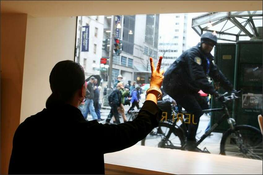 Susan Harris, co-manager of Jeri Rice, a clothing store downtown, flashes the peace sign to protesters and a passing Seattle Police officer.