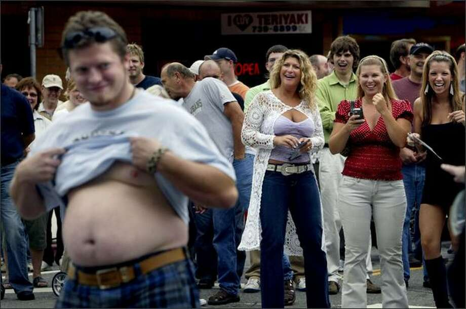Ryan Carlyle of Monroe shows off his beer belly as Debra Churchill, left, Melissa Olson and Mandy Pemberton of Kirkland cheer during a contest to find the most exceptional belly in the crowd gathered for the Kirkland Classic Car Show.Rogers:Covering the car show, I knew I needed more than just pictures of cars to pad an expected photo gallery. When I heard a master of ceremonies call for contestants in a beer belly competition, I knew there would be a picture there. The best reactions from these women were blocked by passers-by, but this worked well enough to make me giggle while I edited it. Photo: Andy Rogers, Seattle Post-Intelligencer
