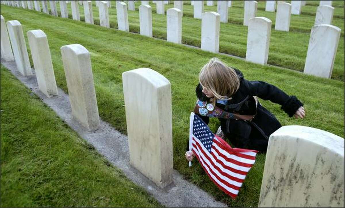 Maddie Powers, 9, a Brownie with Troop 2238 in Mountlake Terrace, plants a flag at one of more than 5,000 gravestones at Veterans' Memorial Cemetery, adjacent to Evergreen-Washelli Cemetery in Seattle. Powers and other Girl Scouts visited the cemetery after taking part in its 58th annual Veterans Day Service of Remembrance.Rogers: I shot a full Veterans Day service at this cemetery, but thought I'd follow these scouts around afterward to get an extra picture or two for a photo gallery. I think this flag was pretty much the last of about 50 that they placed throughout the markers. I was walking toward this girl in the classic coat and she toward me, when she began to slow down and lean. I swooped in shooting and watched between frames as the wind on the flag, her sash, and her graceful arm all moved together into line with the flow of grave markers in my frame.