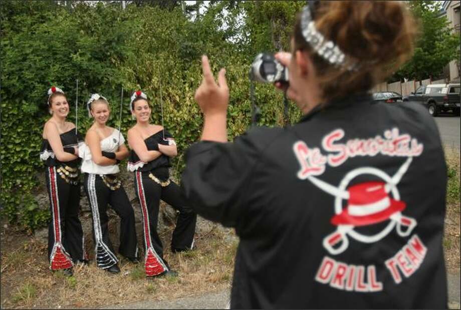 Instructor Katie Merritt takes a picture Wednesday of La Señoritas members Ashley Beach, Nicole Richard and Angela Nadeau, left to right, before the Greenwood Seafair Parade. Photo: Mike Kane/Seattle Post-Intelligencer