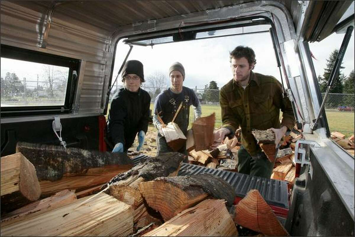 Joe Gabiou (center), owner of the Wobbly Cart Farm, gets help loading free firewood into the back of a truck from his friends Lindsey LaRock, left, of Seattle and Ryan White of Portland in Rochester. Gabiou's farm, located in the Independence Valley, was damaged during last week's flood.