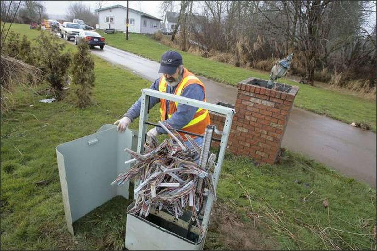 Qwest repairman George Kenny finishes repairs to flood-damaged phone lines near Adna.