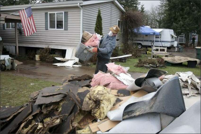 A volunteer adds to a pile of debris in the Tanglewood Trailer Park in Rochester. About twenty homes there suffered major water damage from last week's flooding.