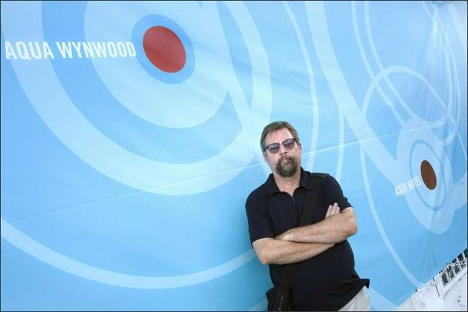 Dirk Park, one of the organizers of the Aqua exhibitions, poses in front of a sign for Aqua Wynwood and Aqua Hotel exhibition spaces at the Aqua Wynwood location in Miami Beach on Dec. 7. (Jacek Gancarz photo)