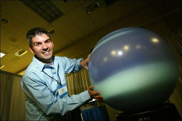Lead researcher Hrvoje Benko shows off Microsoft's Multi-Touch Spherical Display. Photo: Karen Ducey/Seattle Post-Intelligencer