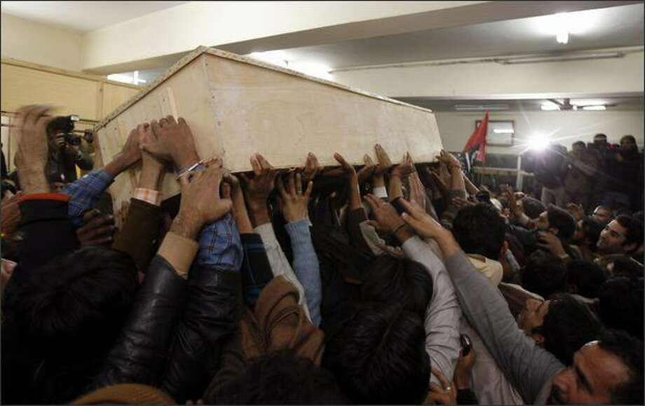 The body of former Prime Minister Benazir Bhutto is carried out of Rawalpindi General Hospital on Thursday in Rawalpindi, Pakistan. The opposition leader has died from a bullet wound to the neck after speaking at a rally in the northern city where an estimated 15 people were left dead by the explosion, a party official and Bhutto's husband have been quoted as saying. Photo: Getty Images