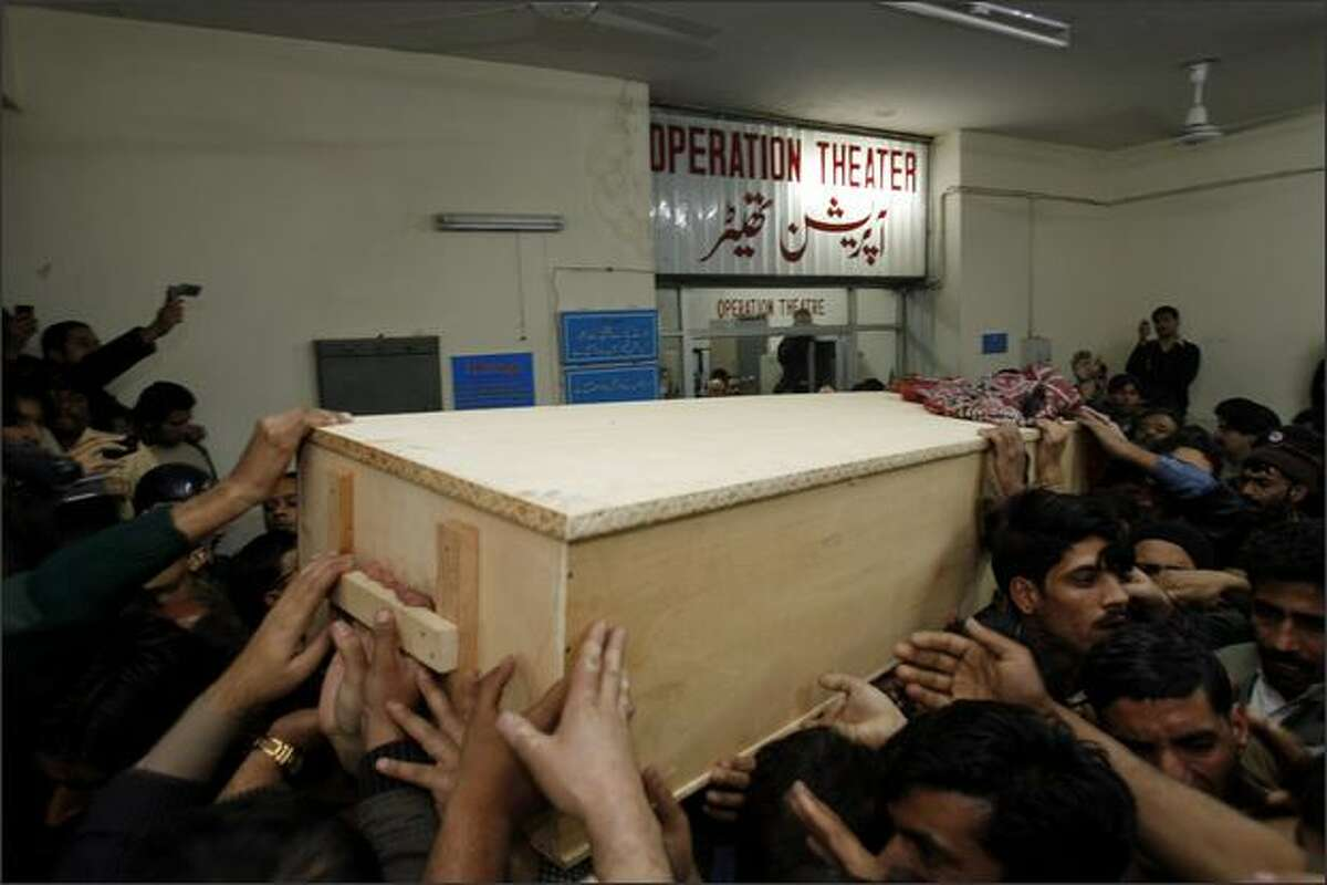 The body of former Prime Minister Benazir Bhutto is carried out of Rawalpindi General Hospital on Thursday in Rawalpindi, Pakistan. The opposition leader has died from a bullet wound to the neck after speaking at a rally in the northern city where an estimated 15 people were left dead by the explosion, a party official and Bhutto's husband have been quoted as saying.