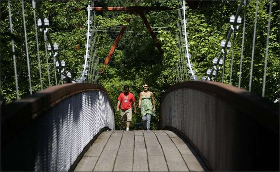 From Main Street, a suspension bridge over the Skagit River leads Jonathan and Christel Henson of Port Townsend to the half-mile-long Trail of the Cedars. Photo: Andy Rogers/Seattle Post-Intelligencer