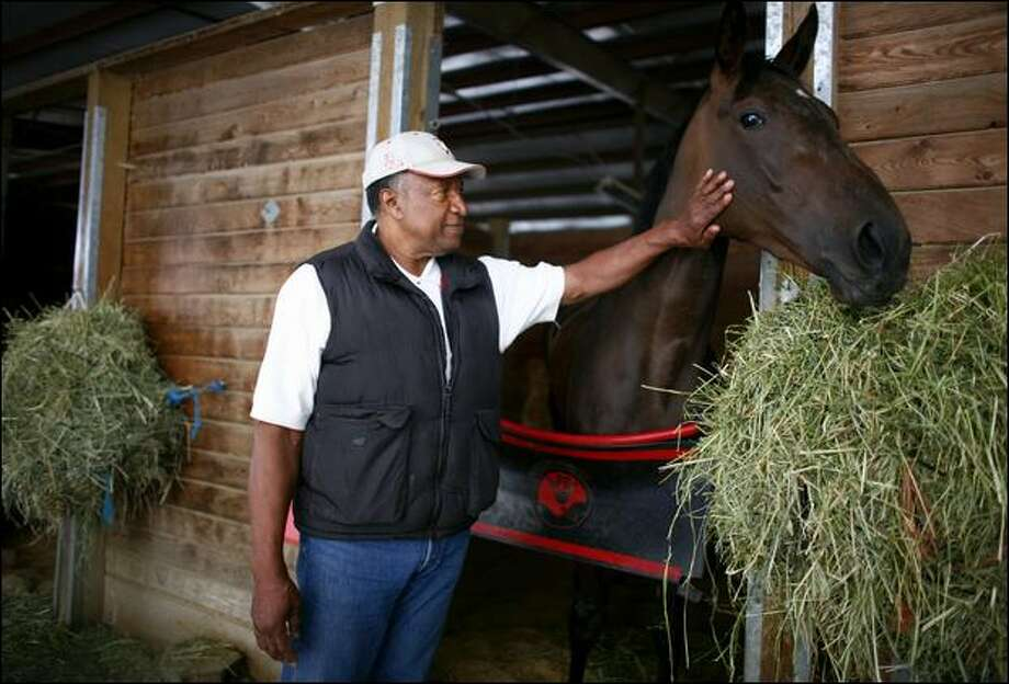 Junior Coffey, a former UW and NFL running back, interacts with Mimi's Road Warrior, one of several racehorses he trains at Emerald Downs. Photo: Joshua Trujillo/Seattle Post-Intelligencer