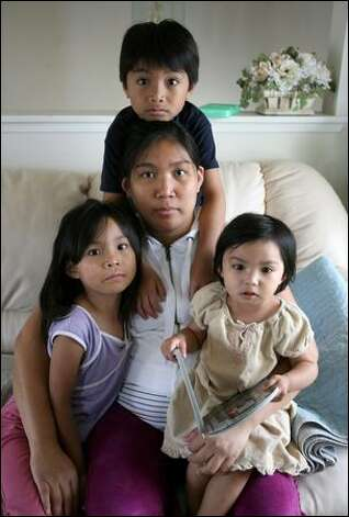 Michelle Miran with her children, clockwise from top, Cedric, 6, Nyssan, 2, and Audrey, 4, are in danger of losing their Tacoma home because of mortgage problems. The family is fighting foreclosure and suing their mortgage broker and lender. Photo: Scott Eklund/Seattle Post-Intelligencer