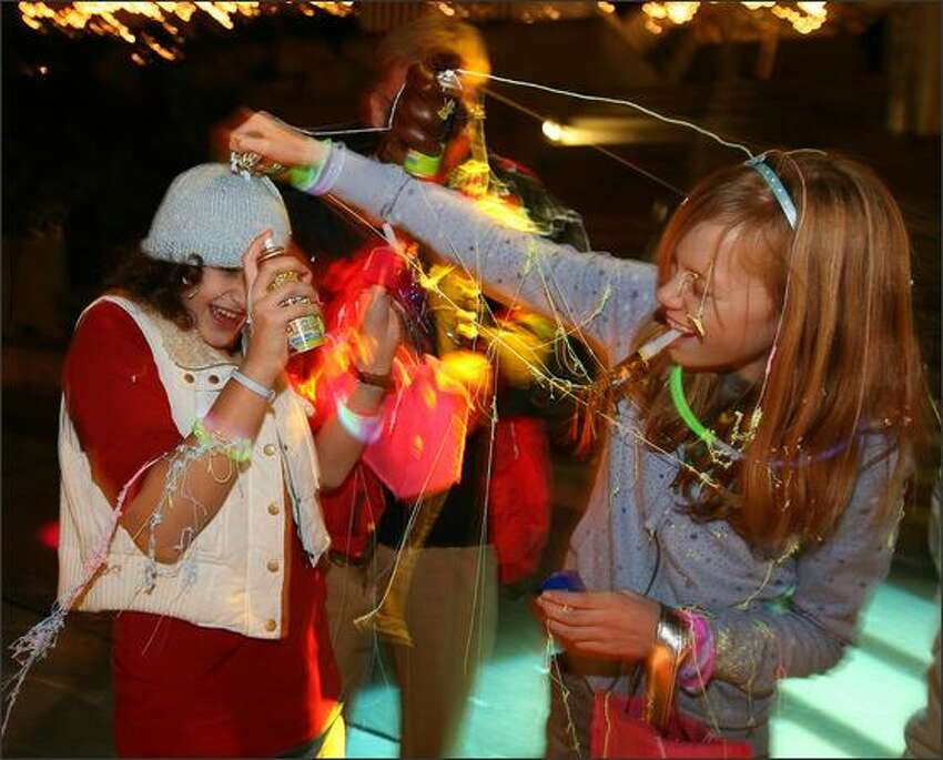 Hannah Tyler, right, the first baby born at Virginia Mason Hospital on Jan. 1, 1996, joyfully applies silly string to her friend Camille Pierson as Hannah's dad, Jeff, in background, counterattacks during Hannah's midnight birthday celebration at Seattle Center.