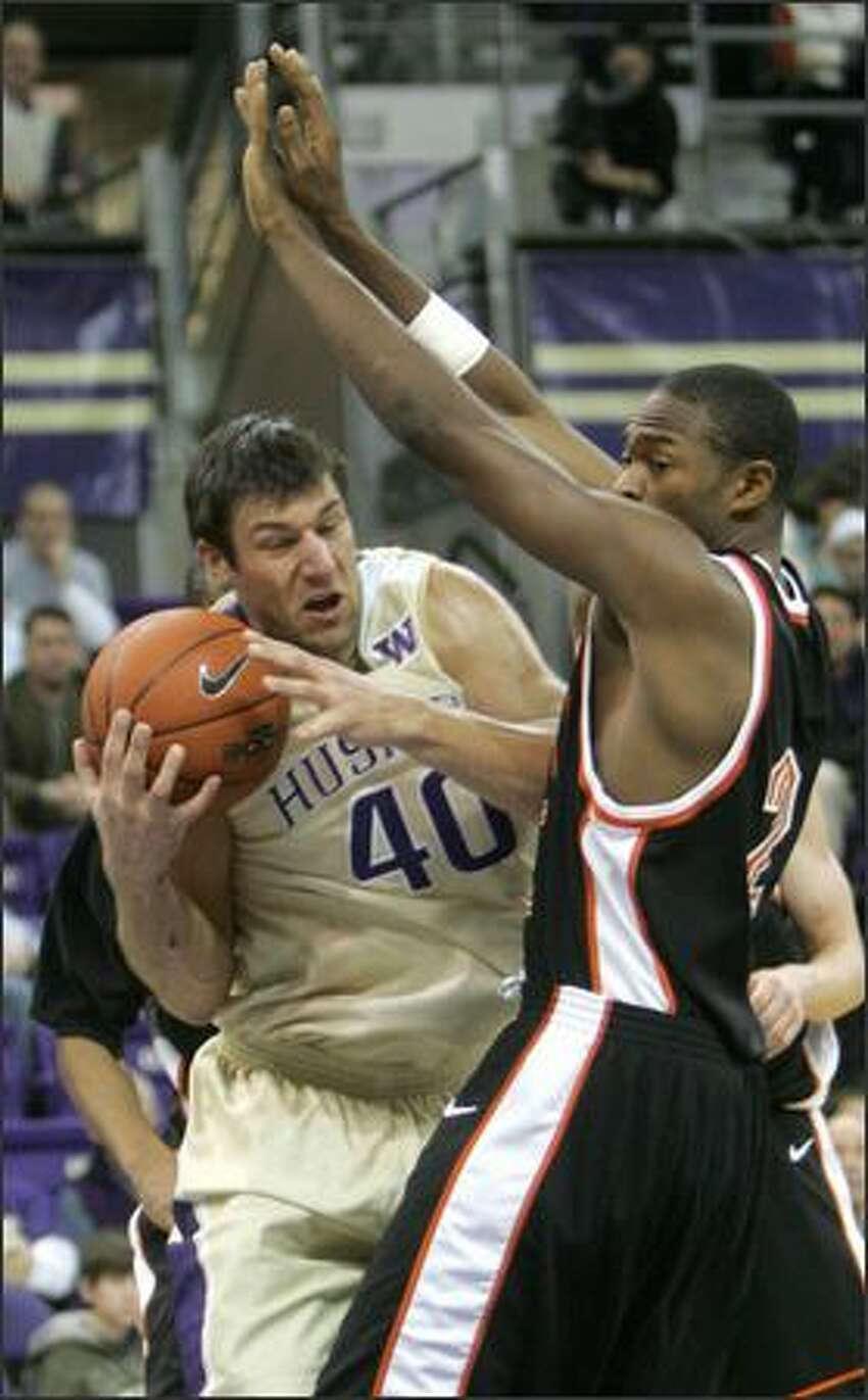 The Huskies' Jon Brockman works under the basket Monday against Idaho State's Chron Tatum. Brockman had 21 points and 11 rebounds.