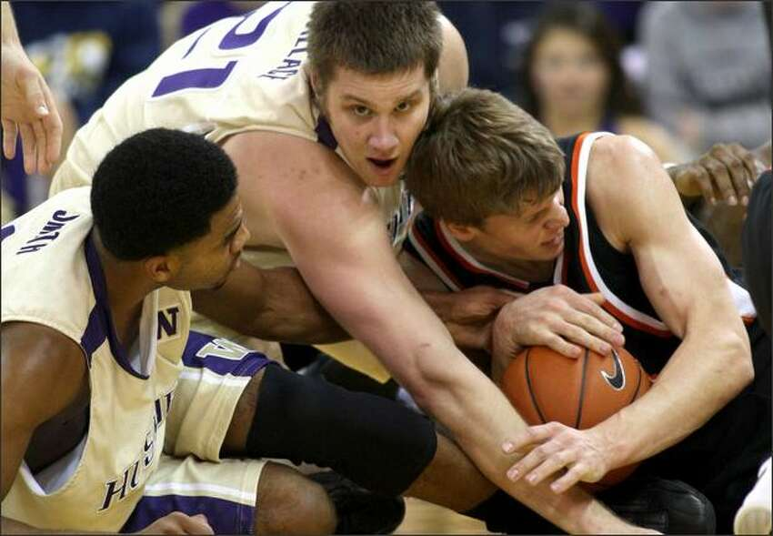 Washington's Joel Smith, left, and Artem Wallace wrestle for a loose ball with Idaho State's Matt Stucki.