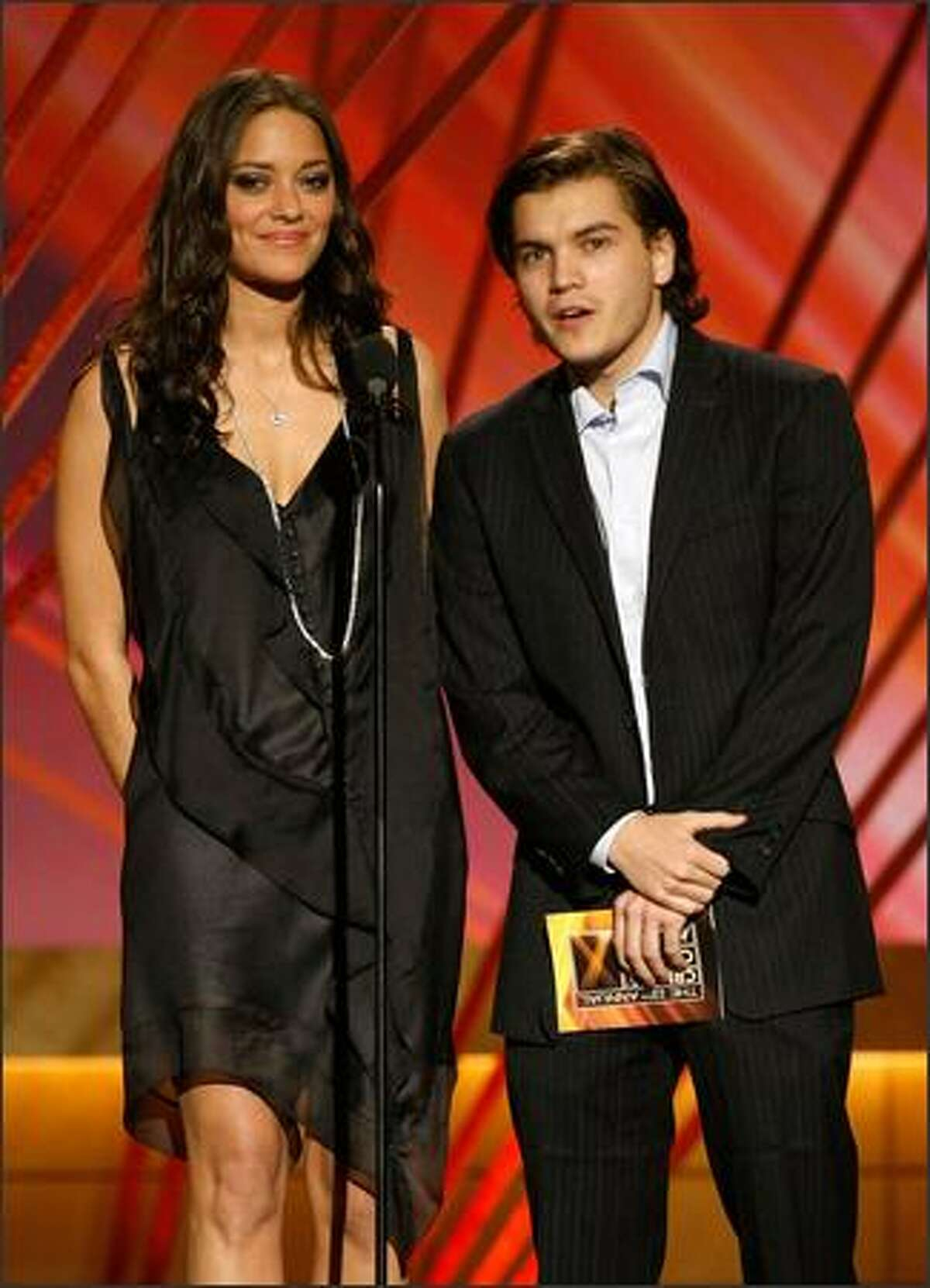 Presenters Marion Cotillard (L) and Emile Hirsch present the Acting Ensemble Award onstage during the 13th annual Critics' Choice Awards held at the Santa Monica Civic Auditorium on Monday in Santa Monica, Calif.