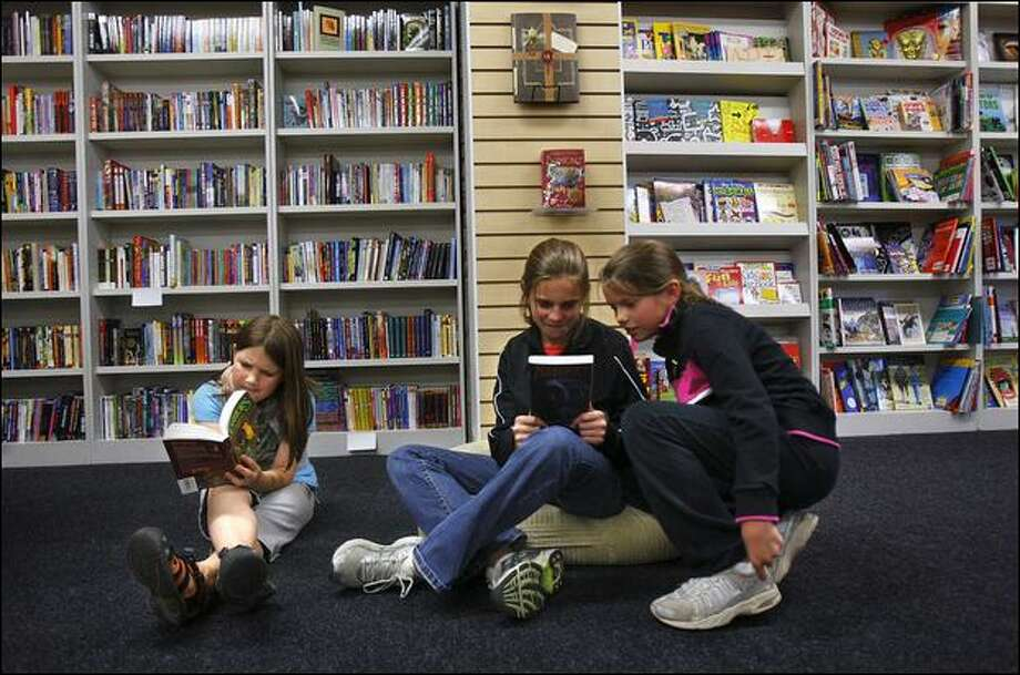 Eight-year-old Kate McCoy of Seattle, left, reads Wednesday at Mockingbird Books, a new children's bookstore in the Greenlake neighborhood. Her cousins, Kelsey Bechtel, 11, center, and her 8-year-old sister Grace, who are visiting from Pennsylvania, look at a new book for themselves. Photo: Andy Rogers/Seattle Post-Intelligencer